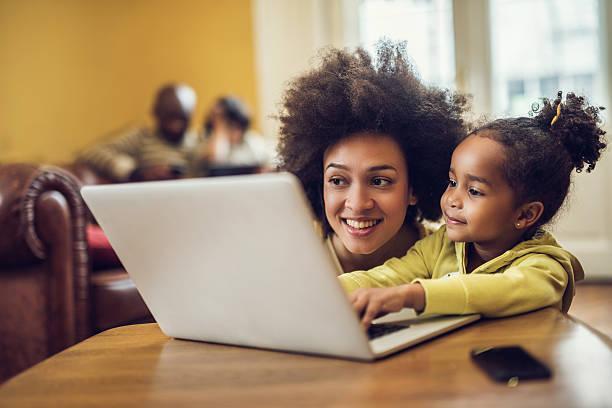 Lächelnden afroamerikanischen Mutter und Tochter mit laptop zu Hause fühlen. – Foto