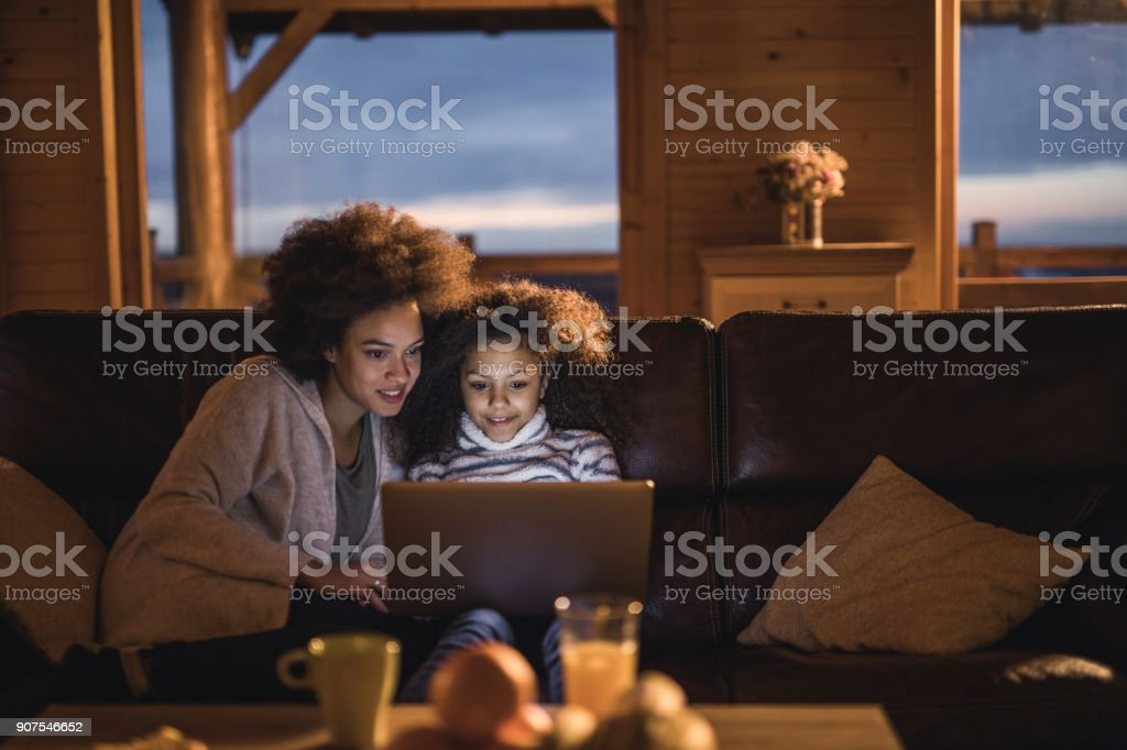 Smiling African American mother and daughter using laptop on sofa at home. stock photo