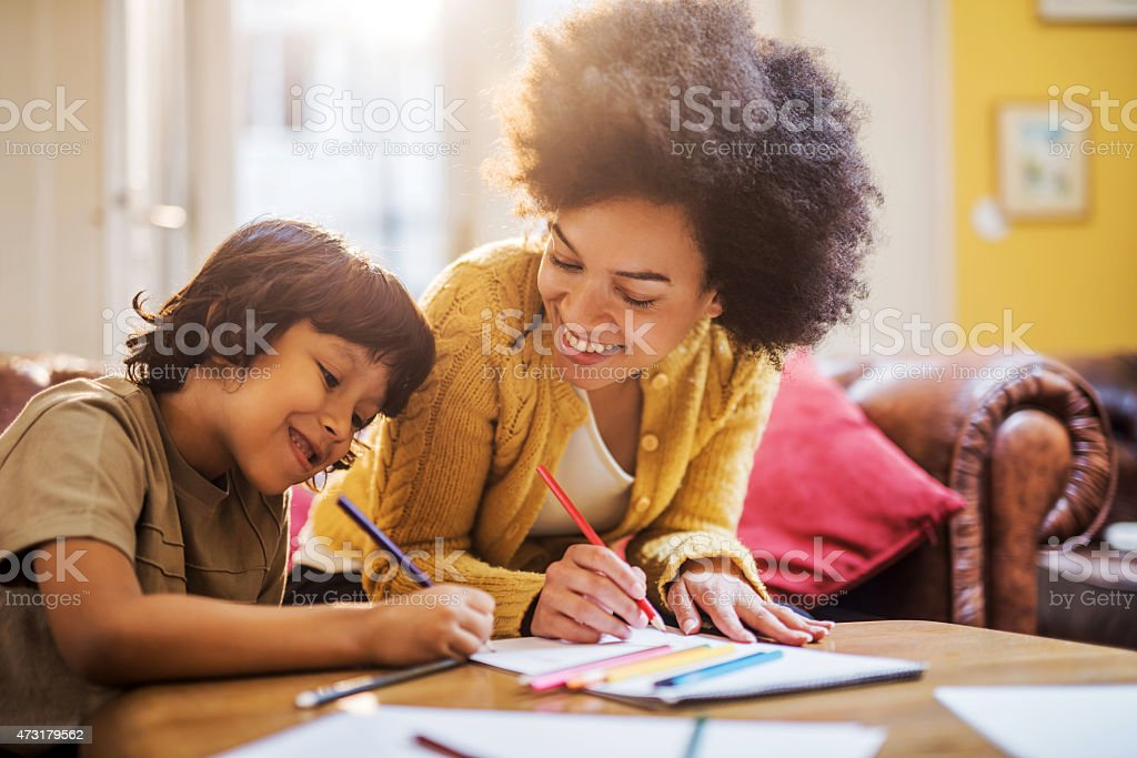 Smiling African American mother and son coloring together. stock photo