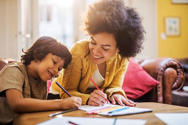 Lächelnden afroamerikanischen Mutter und Sohn zusammen Färben. – Foto