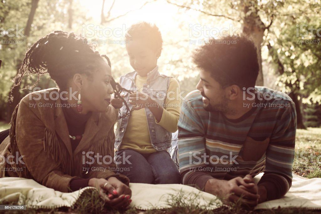 Smiling African American parents lying down in nature and talking with little daughter. royalty-free stock photo