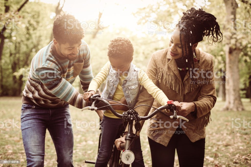 Smiling African American parents teaching their little girl to driving bike in park. royalty-free stock photo