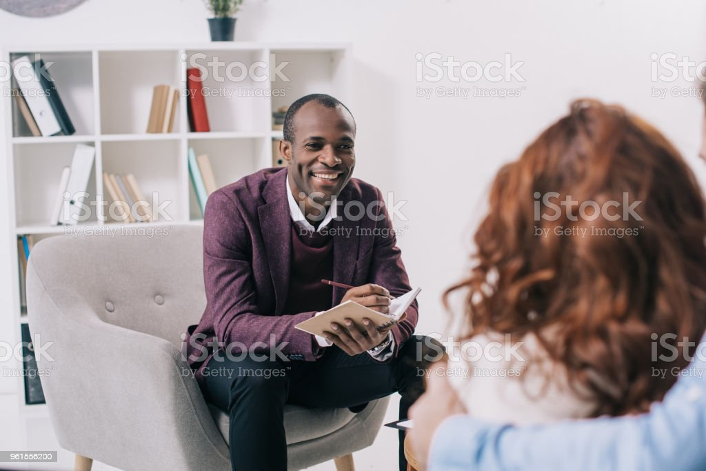 Smiling african american psychiatrist talking to young couple stock photo