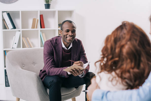 smiling african american psychiatrist talking to young couple - psychiatrist stock photos and pictures