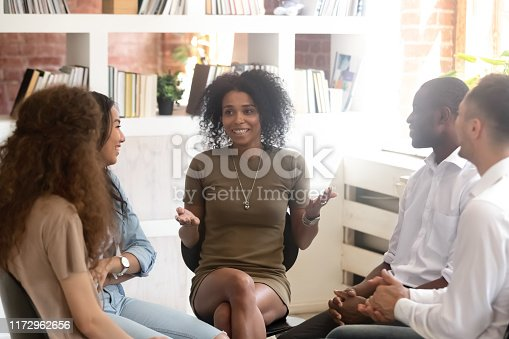 511741068 istock photo Smiling African American psychologist coach speaking with diverse people 1172962656