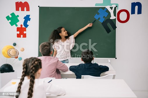 istock Smiling african american schoolgirl pointing at chalkboard while classmates studying at desks 813769394