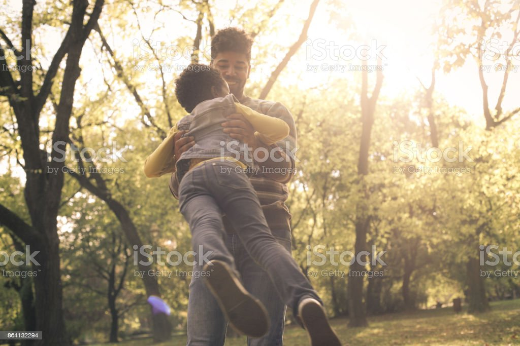 Smiling African American single father in park holding his daughter and rotate in circle. royalty-free stock photo