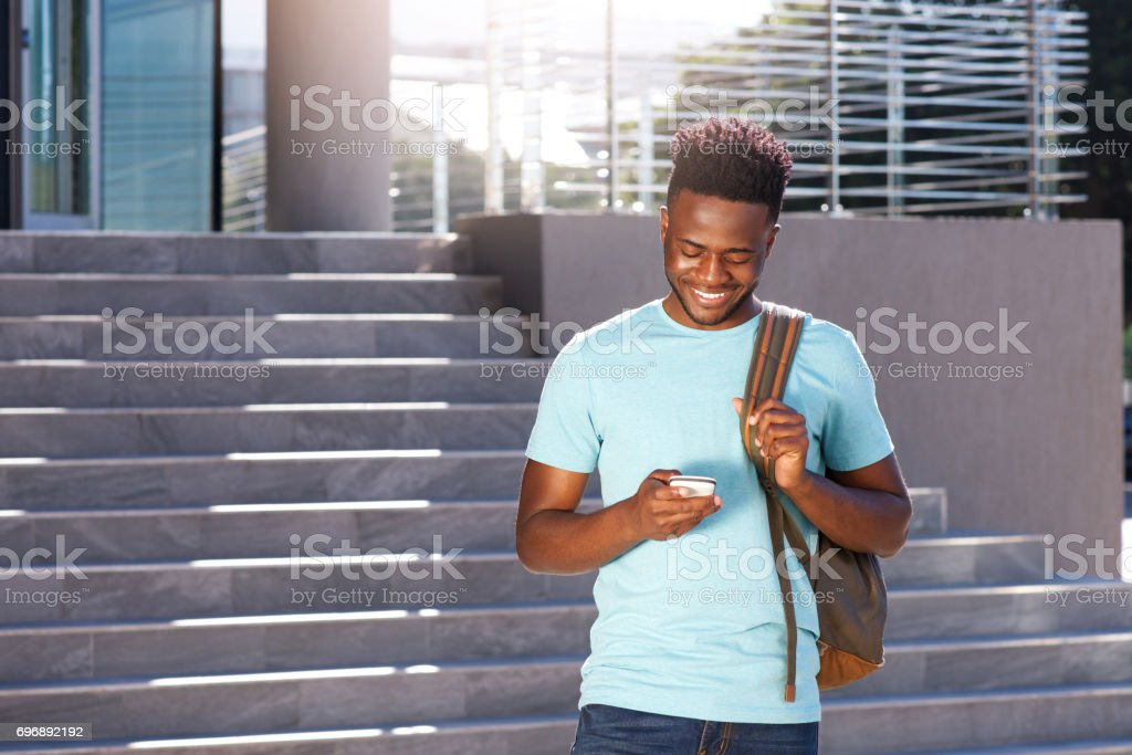 smiling african american student looking at cellphone stock photo