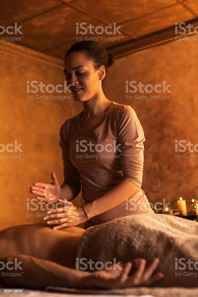 Smiling African American therapist massaging man's back. stock photo
