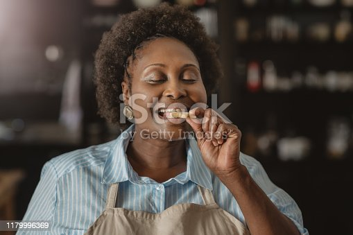 Smiling African American woman standing with her eyes closed in her kitchen at home taking a bite from a cookie