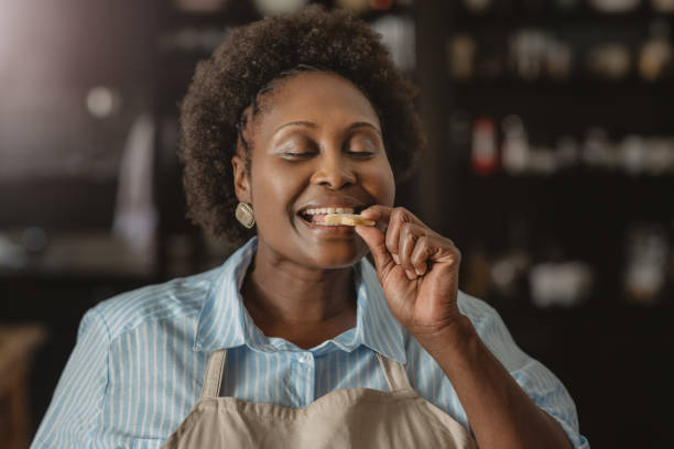 Smiling African American woman biting into a cookie at home stock photo