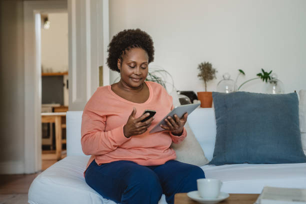 Lächelnde afroamerikanische Frau beim Surfen online mit einem digitalen Tablet – Foto