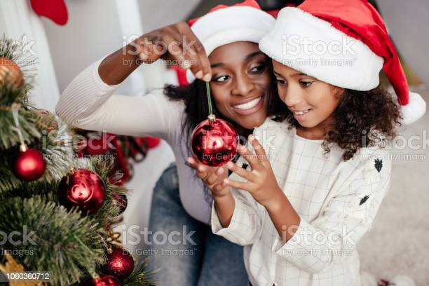 Smiling african american woman in santa claus hat helping daughter to picture id1060360712?b=1&k=6&m=1060360712&s=612x612&h=kyyrr3ddheqsmjbzijeosccak3n5q9yo0gvm81b15jc=