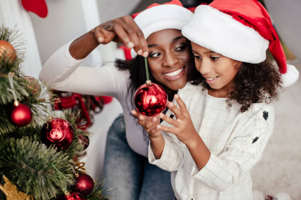 smiling african american woman in santa claus hat helping daughter to decorate christmas tree at home - family christmas imagens e fotografias de stock