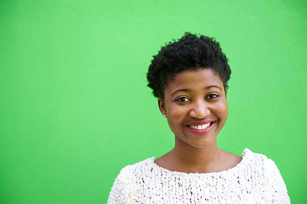 Smiling african american woman on isolated green background Close up portrait of a smiling young african american woman isolated on green background background color stock pictures, royalty-free photos & images