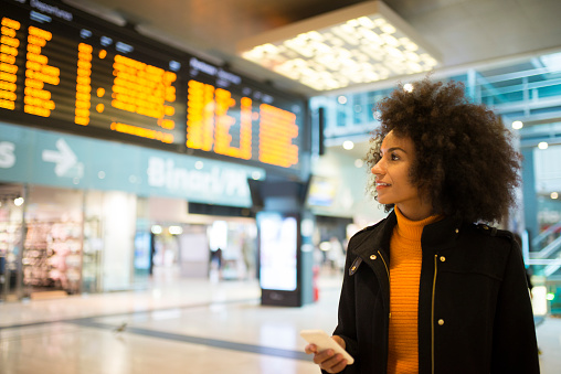 African American woman at the train station checking the departure board