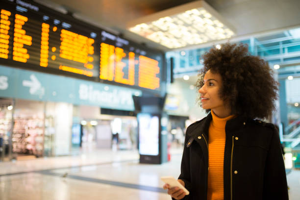 Smiling African American woman. African American woman at the train station checking the departure board railroad station stock pictures, royalty-free photos & images