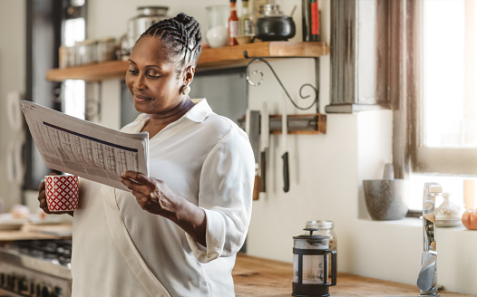 Smiling African American woman reading the newspaper in the morning