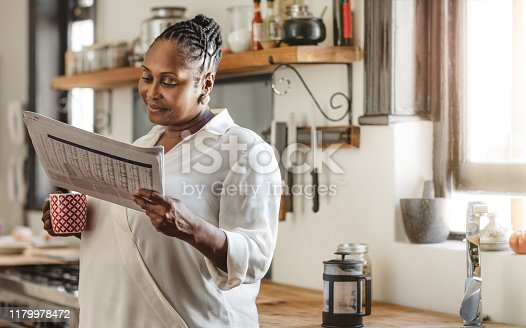 Smiling African American woman drinking a cup of coffee and reading the newspaper while standing in her kitchen in the morning