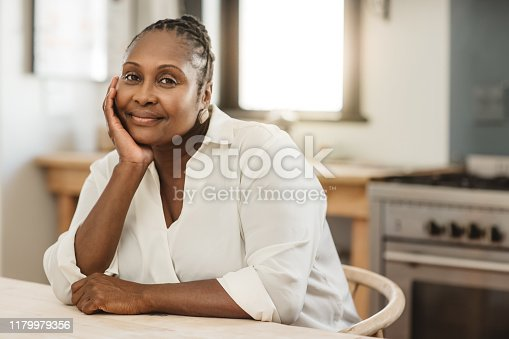 Portrait of a mature African American woman smiling contently while sitting at her kitchen table in the morning