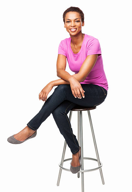 Smiling African American Woman Sitting On Chair - Isolated Full length portrait of a casual smiling African American woman sitting on chair. Vertical shot. Isolated on white. stool stock pictures, royalty-free photos & images