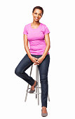 Full length portrait of a casual smiling African American woman sitting on chair. Vertical shot. Isolated on white.