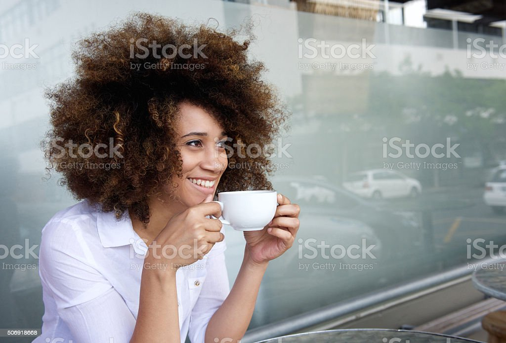 Smiling african american woman sitting with cup of coffee stock photo