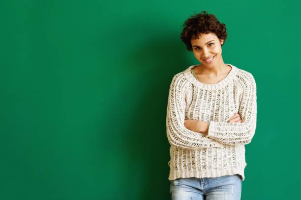 lächelnde afrikanische amerikanische Frau steht gegen grüne Wand mit Denerarmen gekreuzt – Foto