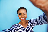 istock smiling african american woman taking selfie against blue wall 857924598