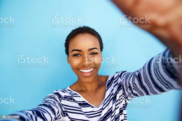 Smiling african american woman taking selfie against blue wall picture id857924598?b=1&k=6&m=857924598&s=612x612&h=do2aajg2r8z2 kcpmekh8gbj ubvdxvzugal7hvf8ko=