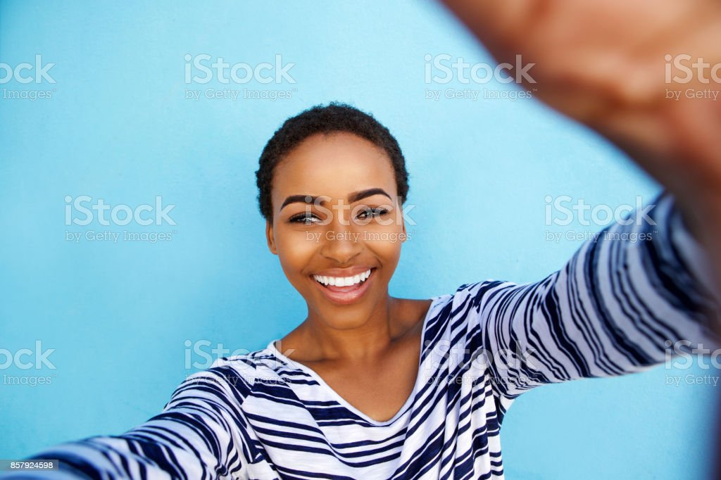 sourire femme afro-américaine prenant selfie contre mur bleu - Photo