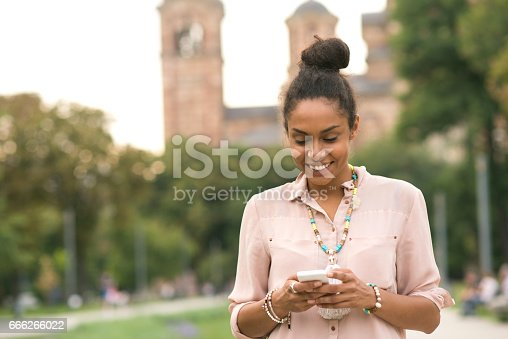 531536422istockphoto Smiling African american woman text messiging 666266022