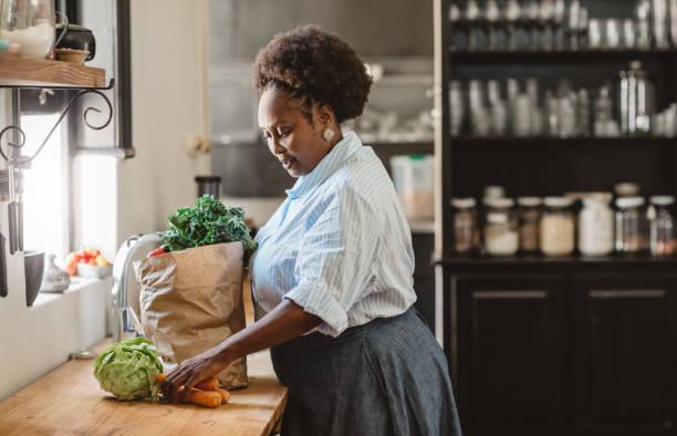 sorridente donna afroamericana che spacchetta generi alimentari nella sua cucina - grocery home foto e immagini stock