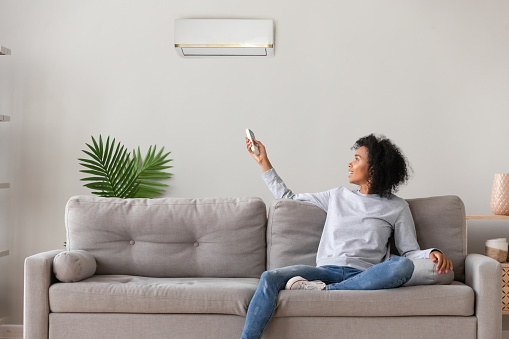 istock Smiling African American woman using air conditioner remote controller 1149308124