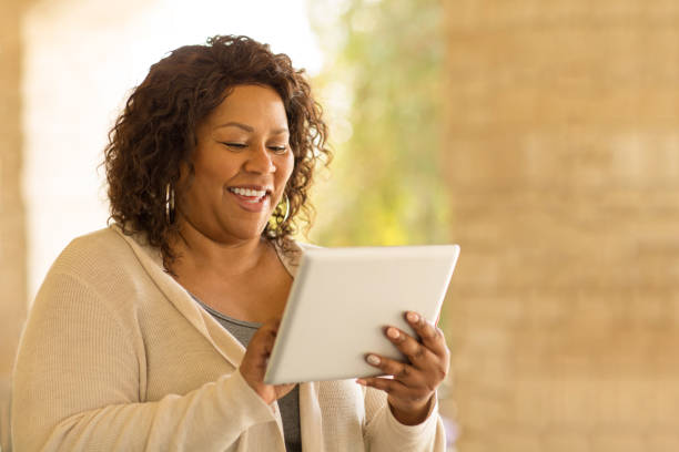 Smiling African American woman working on a tablet. stock photo