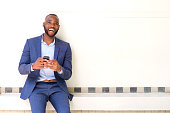 Portrait of smiling african business man sitting against wall with mobile phone