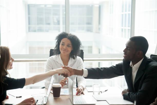 Sonriendo el apretón de manos de empresario africano saludo a empresaria caucásica en reunión del grupo - foto de stock