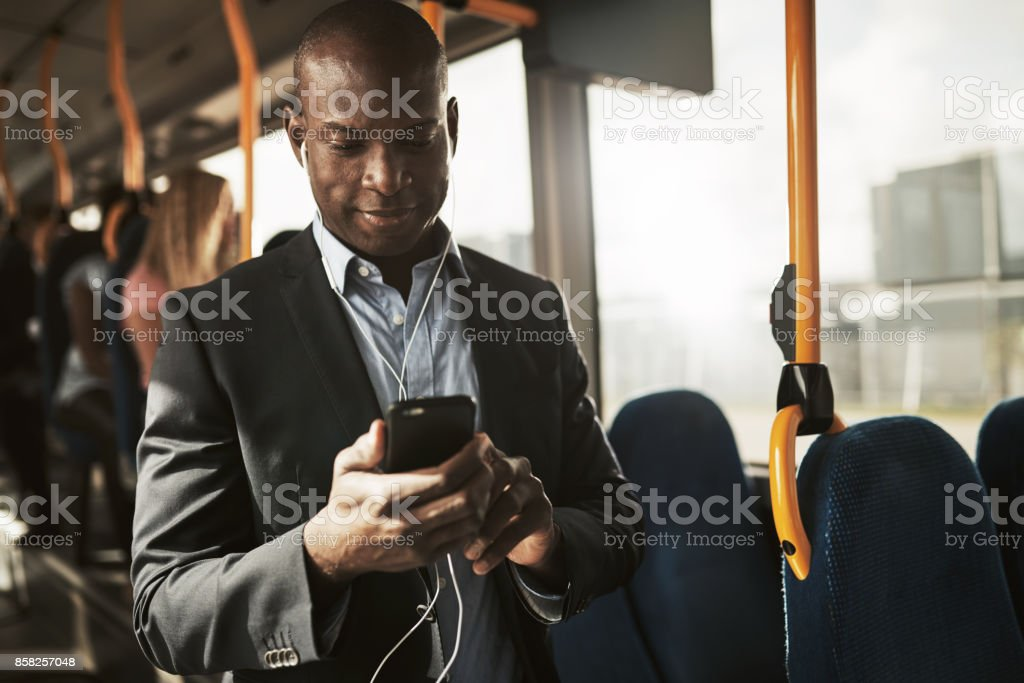 Smiling African businessman listening to music during his morning commute stock photo