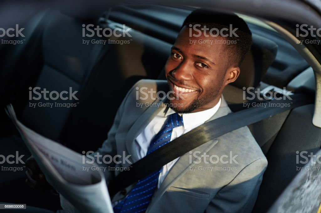Smiling African Businessman Reading Newspaper in Car stock photo