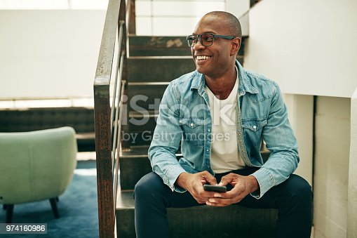 istock Smiling African businessman sitting on office stairs holding a cellphone 974160986