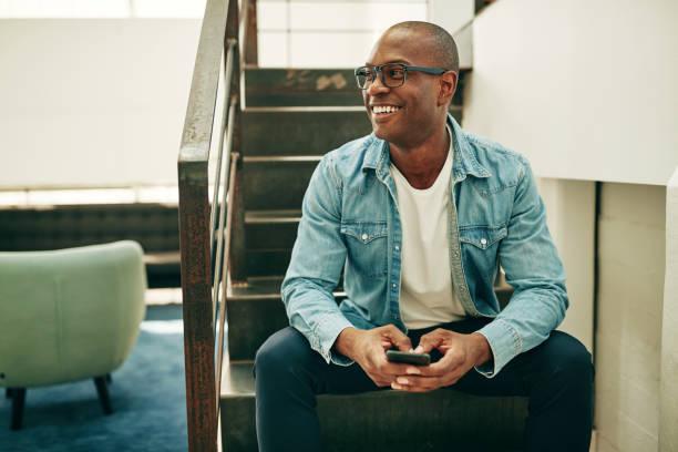 아프리카 사업가 핸드폰을 들고 사무실 계단에 앉아 웃 고 - 청년 남자 뉴스 사진 이미지