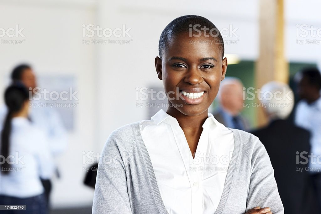Smiling African businesswoman with people in background royalty-free stock photo