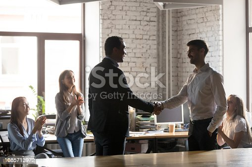 1070271598 istock photo Smiling african ceo promoting motivating successful caucasian worker shaking hands 1085713972