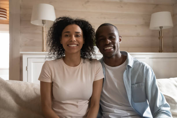Smiling african couple sitting on couch making video call Smiling african couple sitting on couch in living room look at camera making video call chatting with friends talk with relatives online, use modern telecommunication app virtual communication concept young girls on webcam stock pictures, royalty-free photos & images