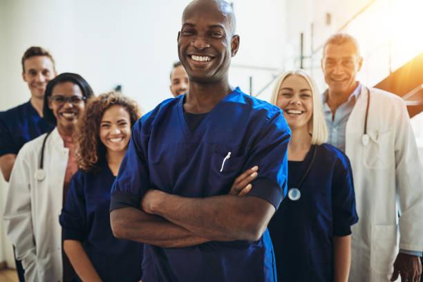 médico africano em pé em um hospital com sua equipe a sorrir - profissional da área médica - fotografias e filmes do acervo
