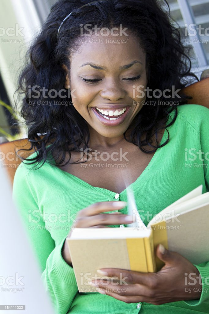 Smiling African ethnicity female reading book and smiling stock photo