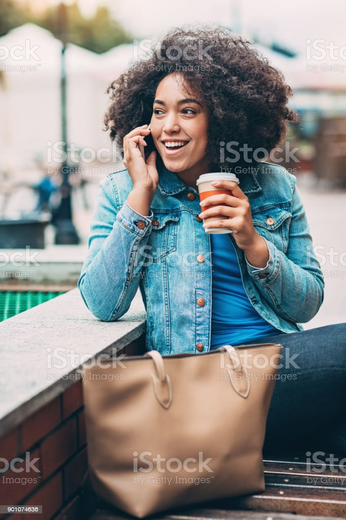 Menina de etnia africana sorridente falando ao telefone - foto de acervo