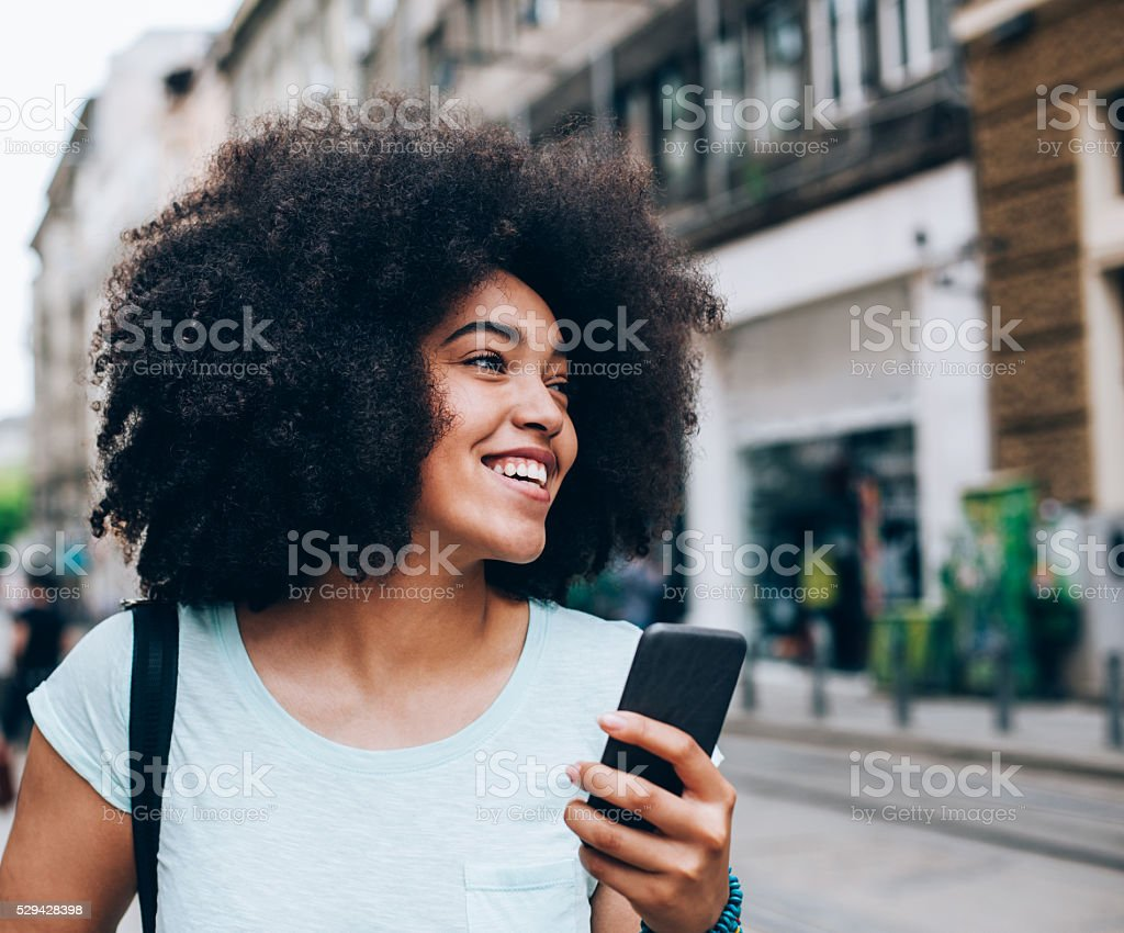 Smiling African ethnicity girl with smart phone stock photo