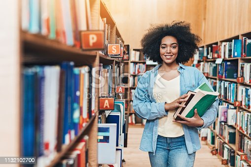 istock Smiling African ethnicity student in the library 1132102700