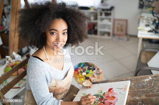 istock Smiling african fine artist working in studio 1159909834